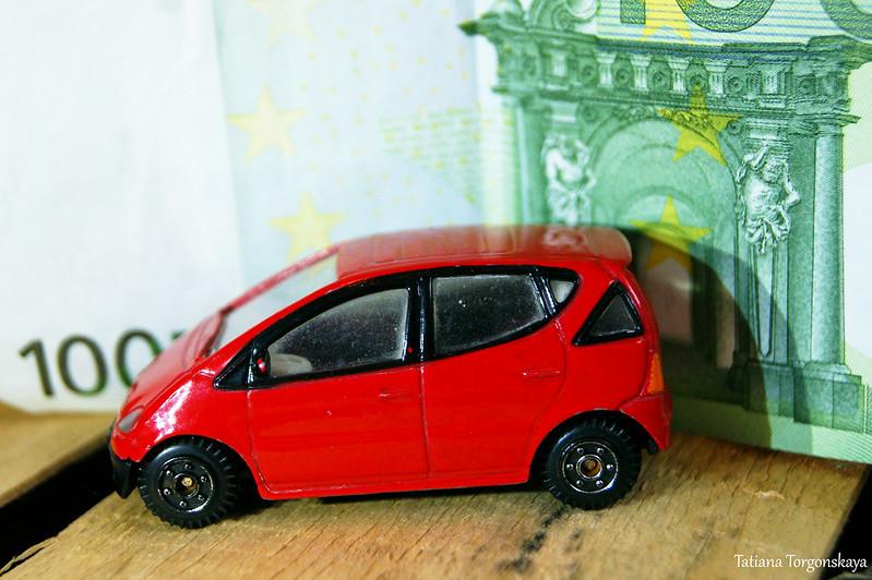 Красное авто на фоне 100 евро