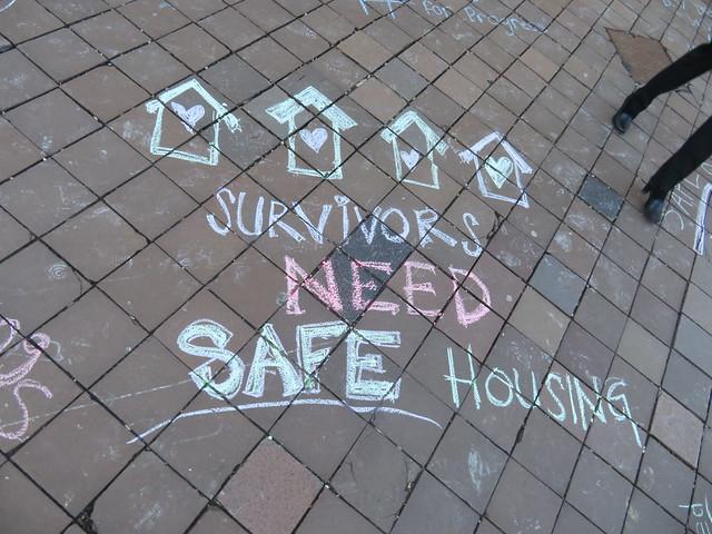 "A sidewalk where ""Survivors Need Safe Housing"" is written in chalk."