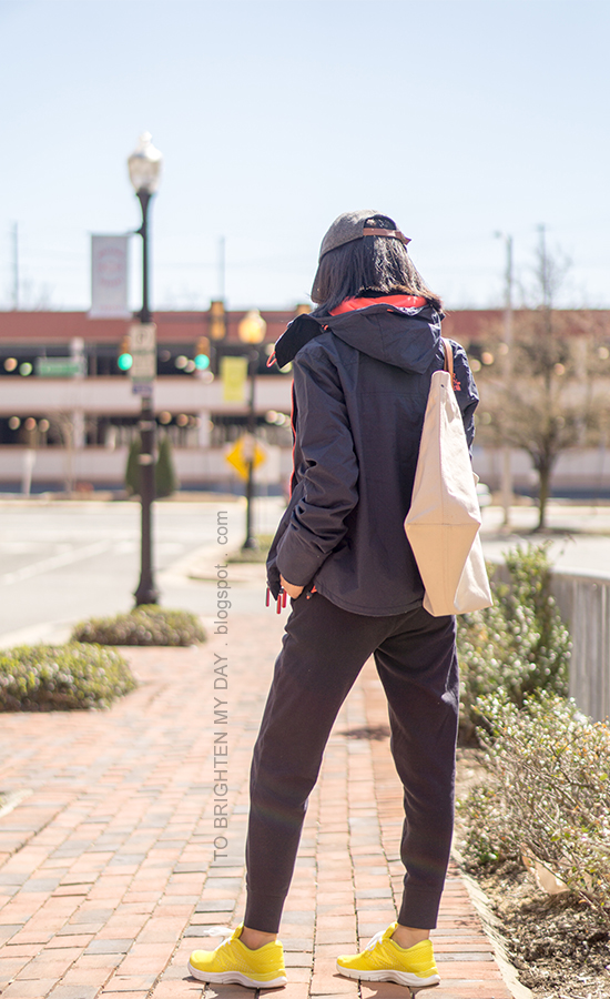 gray baseball cap, navy windcheater jacket, canvas tote, navy sweatpants, yellow sneakers