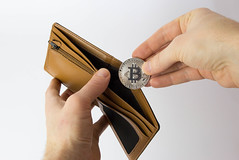 Man putting Bitcoin in his wallet
