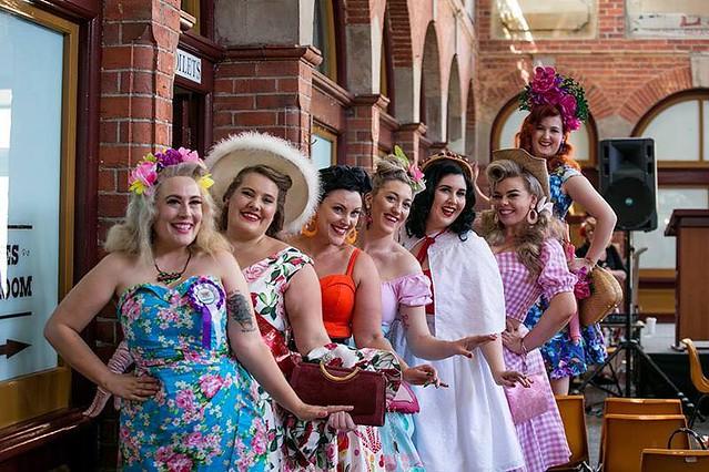 Several women pose in retro costume.