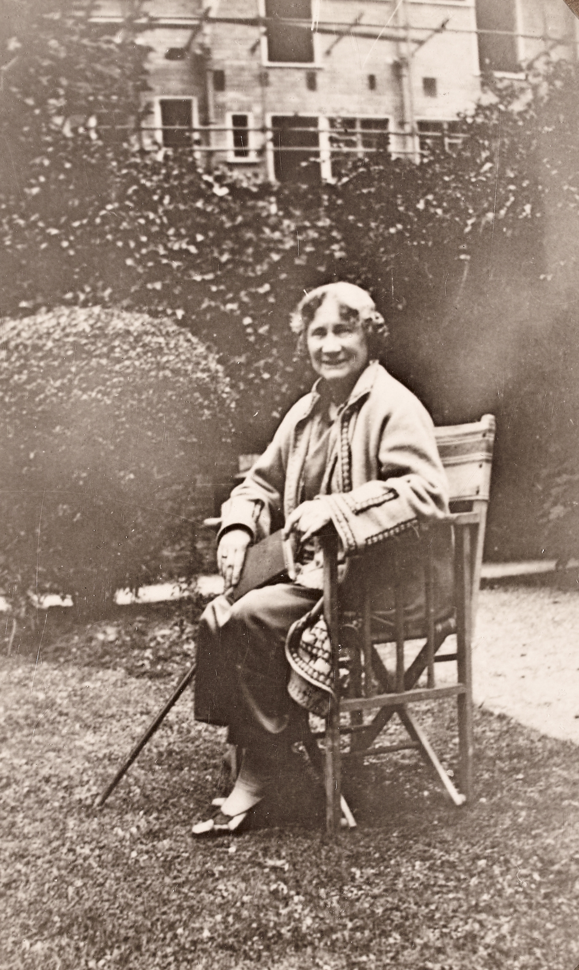 Eleanor Hull, full-length portrait seated in chair, in a garden with a book and a cane