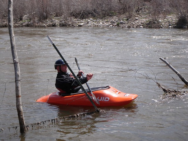 kayaker trying to get past barbed wire fence across river