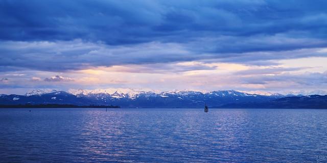 Illuminated Alps behind Lake Constance