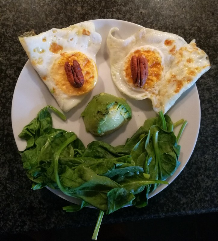 Eggs, avocado, pecan nuts and smiley spinach