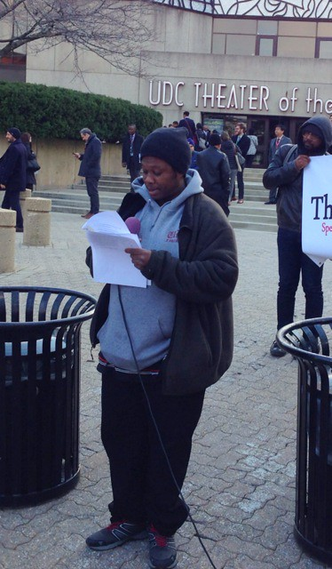 Photo of a man holding a microphone and reading from typed remarks, in front of the UDC Theater of the Arts