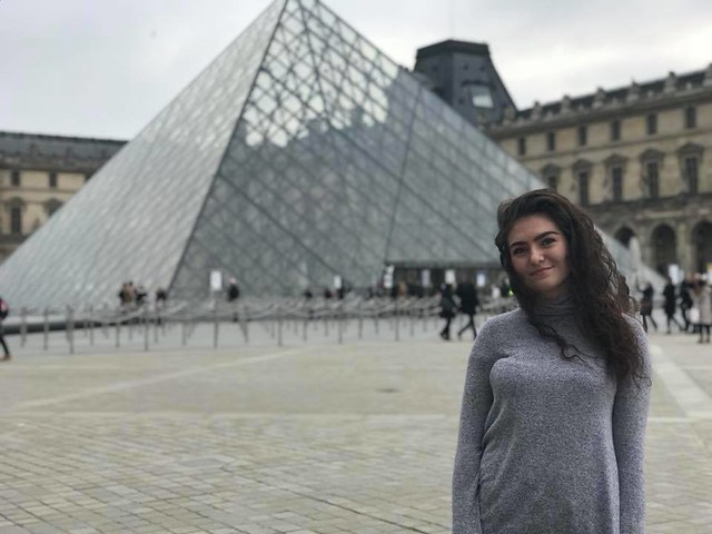 Student standing in front of the Louvre, Paris, France.
