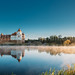 Mir, Belarus. Panoramic Scenic View Of Castle Complex Mir On Sunny Sunrise Sky Background. Panorama Of Morning Fog Over Lake River And Old Towers Are Reflected In Water