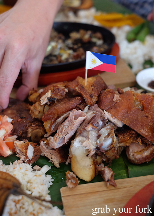 Eating crispy pata deep fried pig trotters for our boodle fight at Sizzling Fillo in Lidcombe Sydney