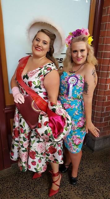 Two women pose in retro costume.