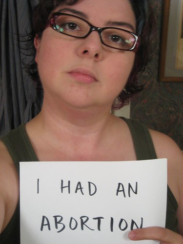 """white woman holding up sign saying """"i had an abortion"""""""