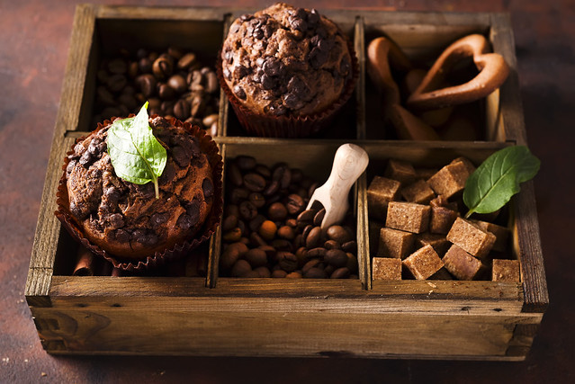 Chocolate muffins on a wooden box with grains of coffee and spices,