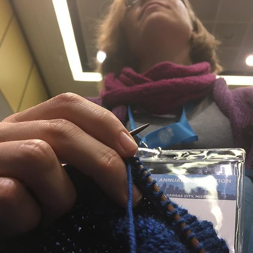 Knitting during a panel presentation.