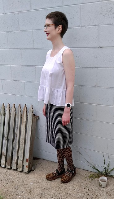 A woman stands in front of a blue brick wall. She wears a white peplum top, navy white stripe knit pencil skirt, and animal print tights and clogs.