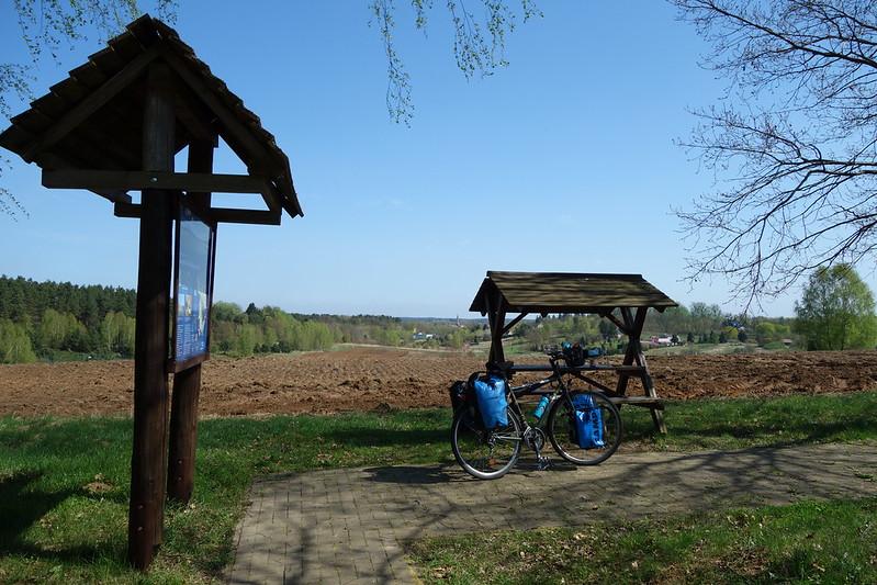 Eine Sitzbank mit Dächlein an einem kleinen Rastplatz auf einem Hügel über Fürstenberg, im Hintergrund bestellt jemand sein Feld. Seitlich steht noch eine Tafel mit Informationen über das Ruppiner Seenland.