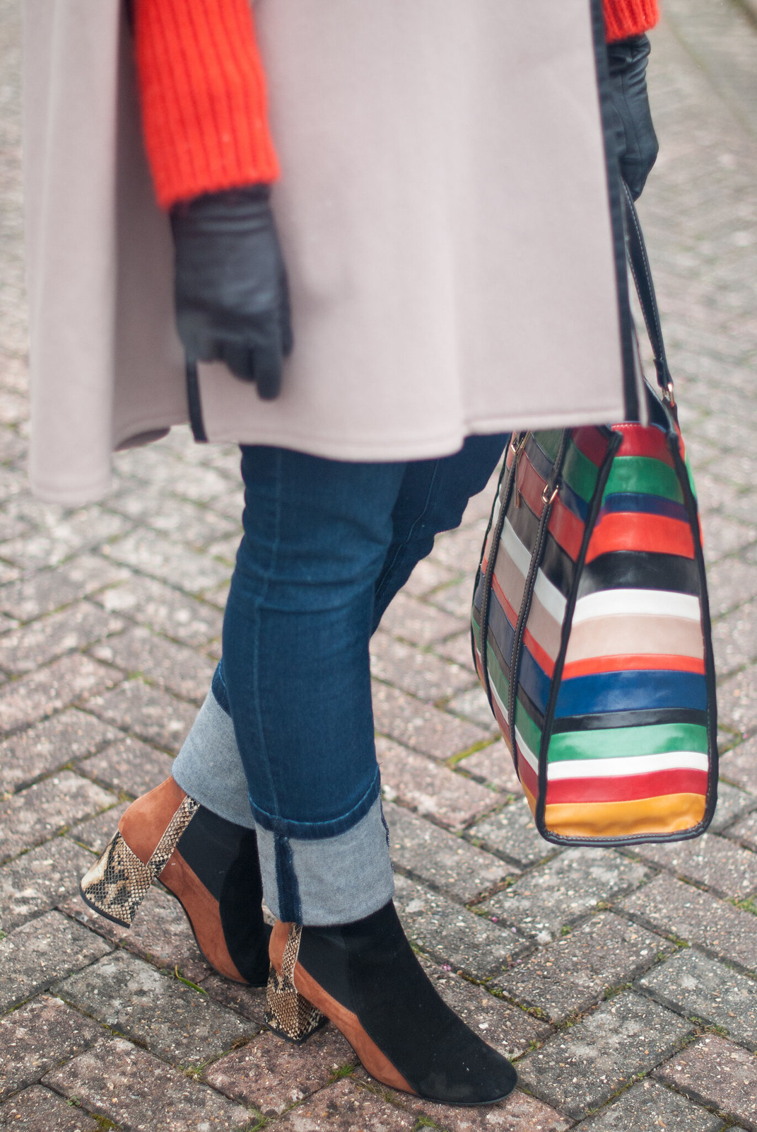 A Parisian Chic Winter Outfit, Over 40 Style \ camel wool cape \ ear muffs \ orange thick knit sweater \ rolled-hem jeans \ two-tone ankle boots \ rainbow-stripe tote bag | Not Dressed As Lamb