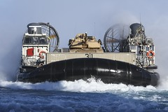 A landing craft air cushion (LCAC) attached to Assault Craft Unit (ACU) 5 transports an M1A1 Abrams tank into the well deck of USS Essex (LHD 2), March 23. (U.S Navy/MCSN Jacob Owen)