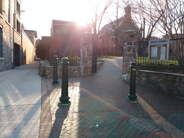 A quiet morning streetscape with the sun rising behind a church building.