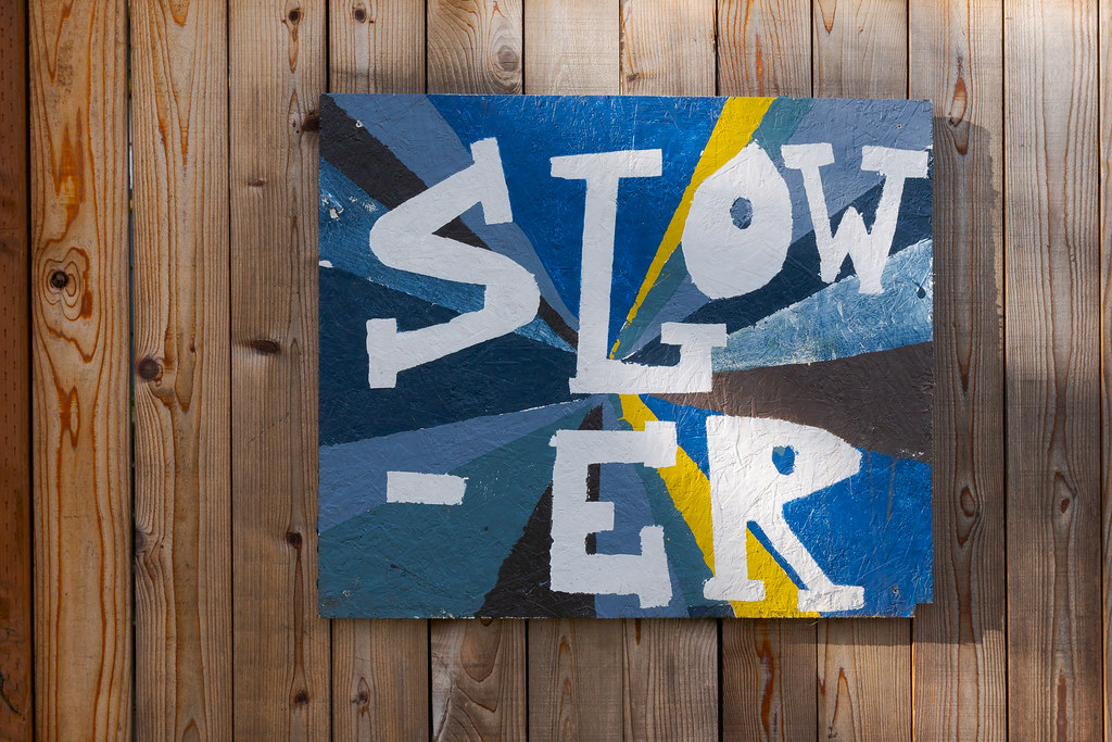 A painting on a fence that says 'Slower'