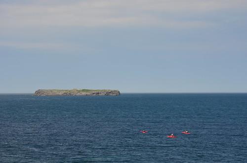 Eine Felseninsel im Meer mit drei kleinen roten Booten.