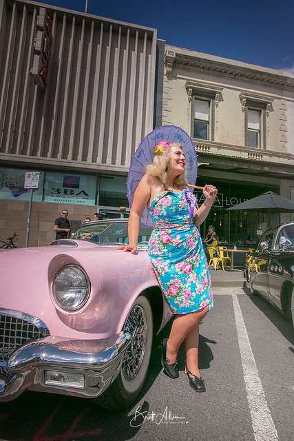 Woman poses in front of a pink vintage car. She wears a retro playsuit, consisting of a bustier top and sarong skirt in a blue tropical print. She holds a parasol.