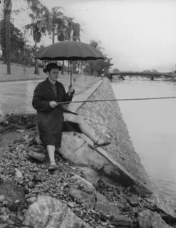 Adrian Zana fishing in the rain at Breakfast Creek, 1952