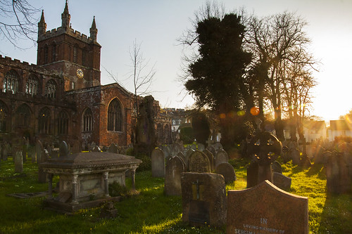 churchoftheholycrossandthemotherofhimwhohungthereon parishchurch church building crediton historic cemetary sunset sunflare flare spring architecture graveyard tombstones graves canon eos50d tamron 1750mm devon middevon cathedral red steeple tree goldenlight daisies clock