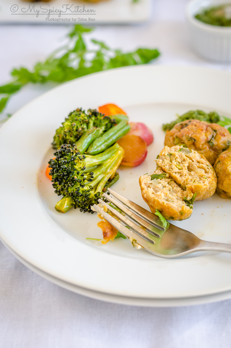 A plate of cut baked chicken kofta with some baked vegetables