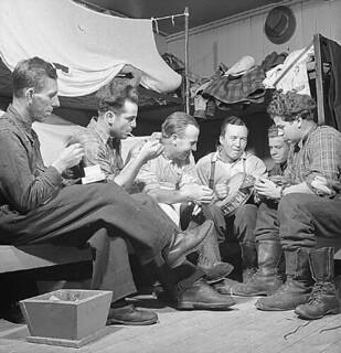 """Loggers in the camp bunkhouse enjoy an evening with a little """"homemade"""" music, Gatineau, Quebec / Des bûcherons se divertissent en soirée dans un dortoir en jouant de la musique improvisée, Gatineau (Québec)"""