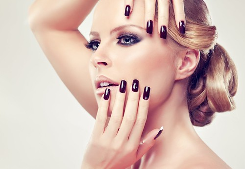 Blonde model in burgundy manicure and stylish hairstyle