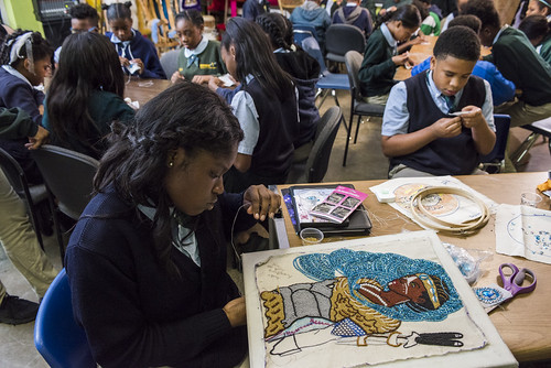 Big Queen Regine works on a large piece while classmates help with the smaller patches on November 16, 2017. Photo by rhrphoto.com.