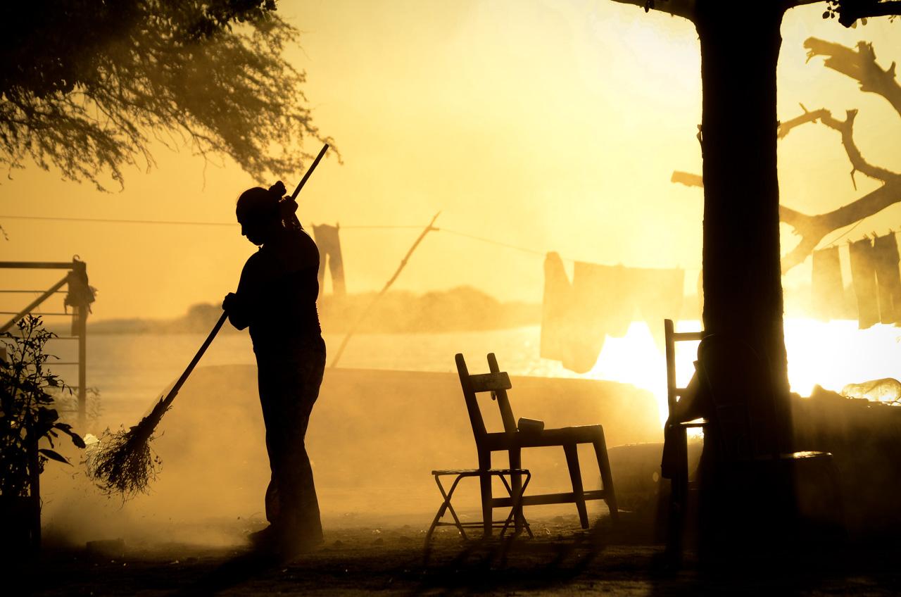 Una señora limpia el patio de su casa con la típica escoba hecha con yuyos y palo de tacuara, en la localidad de Zanjita, departamento de Ñeembucú. (Elton Núñez).