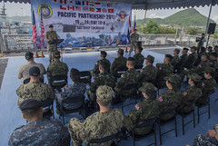 SATTAHIP, Thailand (May 20, 2018) Royal Navy Capt. Peter Olive, Deputy Mission Commander of Pacific Partnership 2018 (PP18), delivers remarks during the opening ceremony of Pacific Partnership 2018 (PP18) Thailand aboard Military Sealift Command expeditionary fast transport ship USNS Brunswick (T-EPF 6). PP18's mission is to work collectively with host and partner nations to enhance regional interoperability and disaster response capabilities, increase stability and security in the region, and foster new and enduring friendships across the Indo-Pacific region. Pacific Partnership, now in its 13th iteration, is the largest annual multinational humanitarian assistance and disaster relief preparedness mission conducted in the Indo-Pacific. (U.S. Navy photo by Mass Communication Specialist 2nd Class Joshua Fulton/Released)