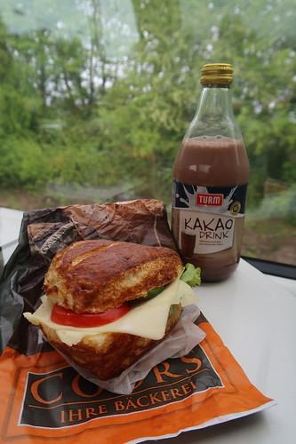 Vegetarisch belegte Laugenecke von der Bäckerei Coors (Osnabrück Hbf) mit Kakao Drink als Frühstück im Zug nach Koblenz