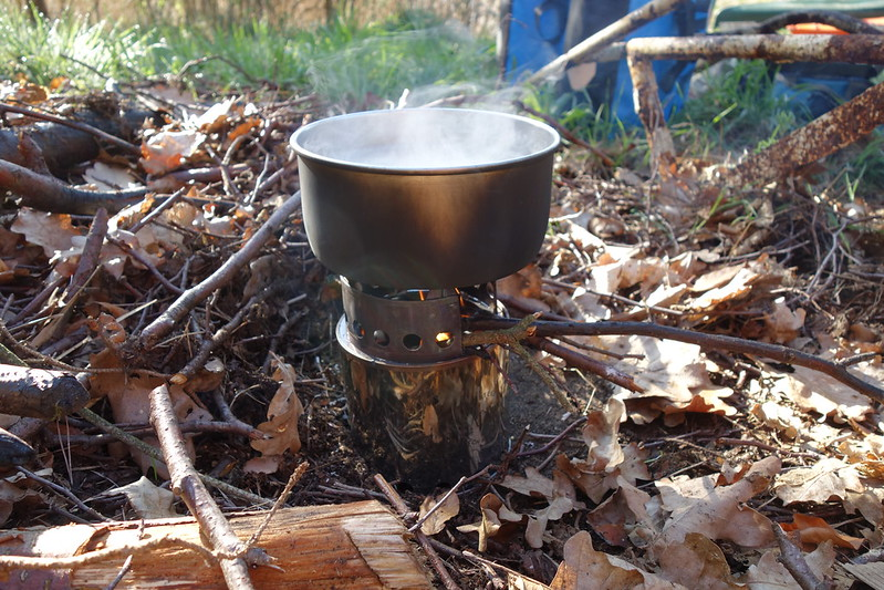 Die Feuerstelle am See ist gerade etwas unordentlich mit Zweigen und Laub bedeckt. Dort habe ich trotzdem meinen kleinen Holzkocher aufgestellt, es ist ein ALB Wood Stove, den ich mir im lokalen Outdoorladen gekauft hatte. Gerade kocht ein Topf Hirse.
