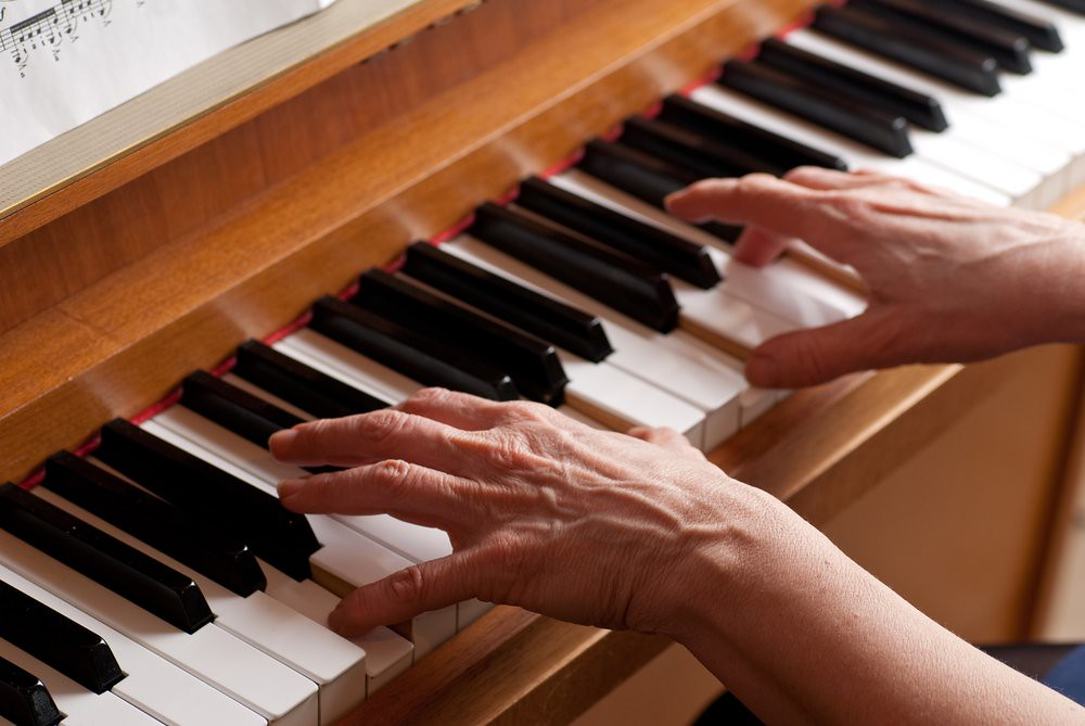 photo of woman's hands playing an upright piano