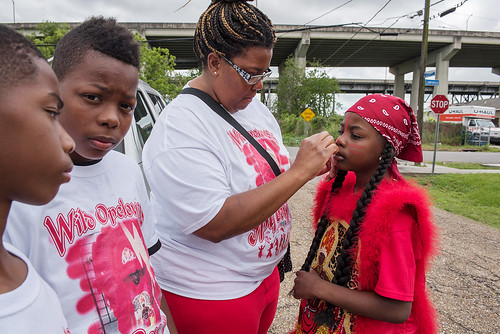 Wild Opelousas Spy Boy Kyllon Martin gets help with his face paint before West Fest parade on April 23, 2017. Photo by Ryan Hodgson-Rigsbee www.rhrphoto.com