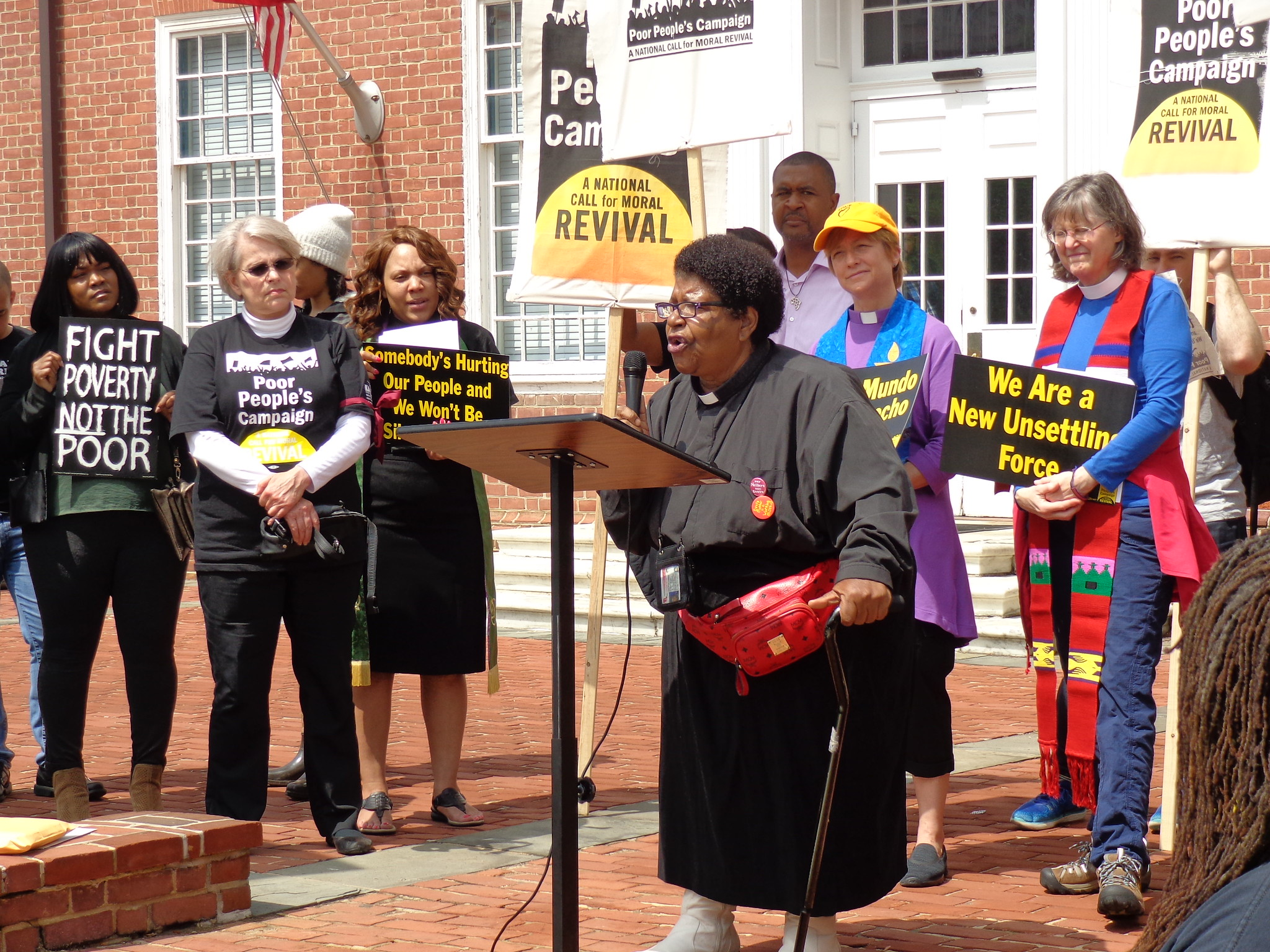 Rev. Annie Chambers, holding a cane and speaking from an outdoor podium. A line of other clergy stand behind her, some in vestments and all holding signs related to the Poor People's Campaign.