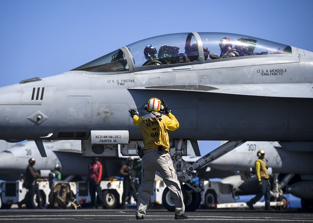 PACIFIC OCEAN (April 19, 2018) Chief Aviation Boatswain's Mate (Handling) Solomon Thompson signals an F/A-18F Super Hornet, assigned to the Fighting Redcocks of Strike Fighter Squadron (VFA) 22, on the flight deck of the aircraft carrier USS Theodore Roosevelt (CVN 71). Theodore Roosevelt is currently underway for a regularly scheduled deployment in the U.S. 7th Fleet area of operations in support of maritime security operations and theater security cooperation efforts. (U.S. Navy photo by Mass Communication Specialist Seaman Bill M. Sanders/Released)