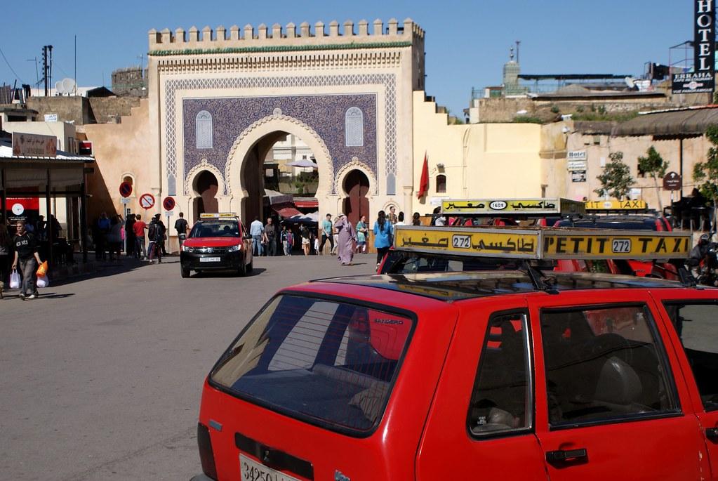 Petit taxi (rouge) devant la porte bleue à Fès au Maroc.