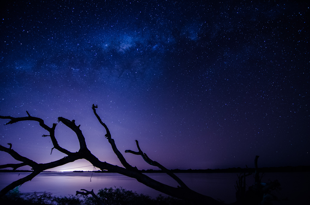 Vista del cielo estrellado y el río Paraguay en febrero de 2018, tomado desde la orilla, en el departamento de Ñeembucú, en el fondo se puede notar las luces de la ciudad argentina de Formosa. (Elton Núñez).