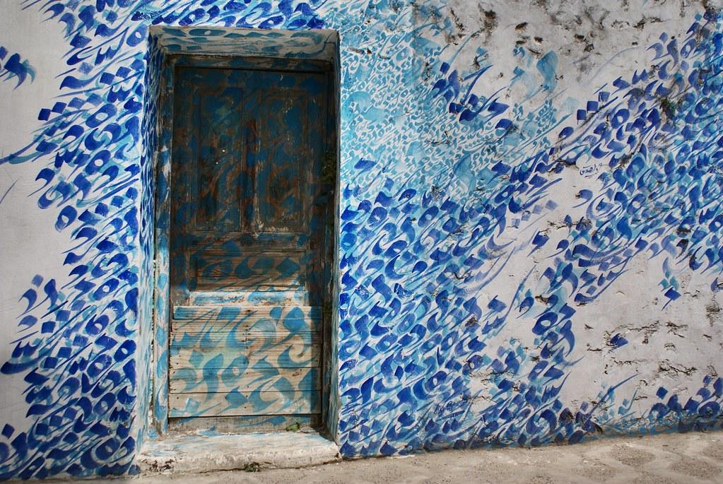 Jolie fresque de street art à Asilah entre calligraphie et ressac de la mer.
