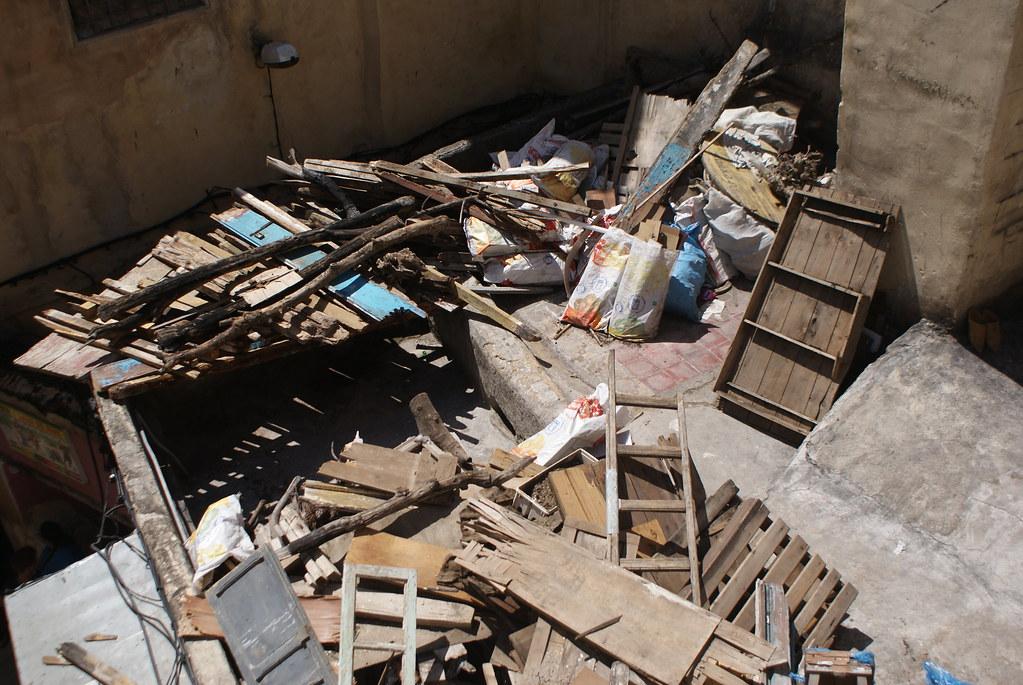 Récupération de bois stocké sur un toit pour alimenter le four d'un artisan.