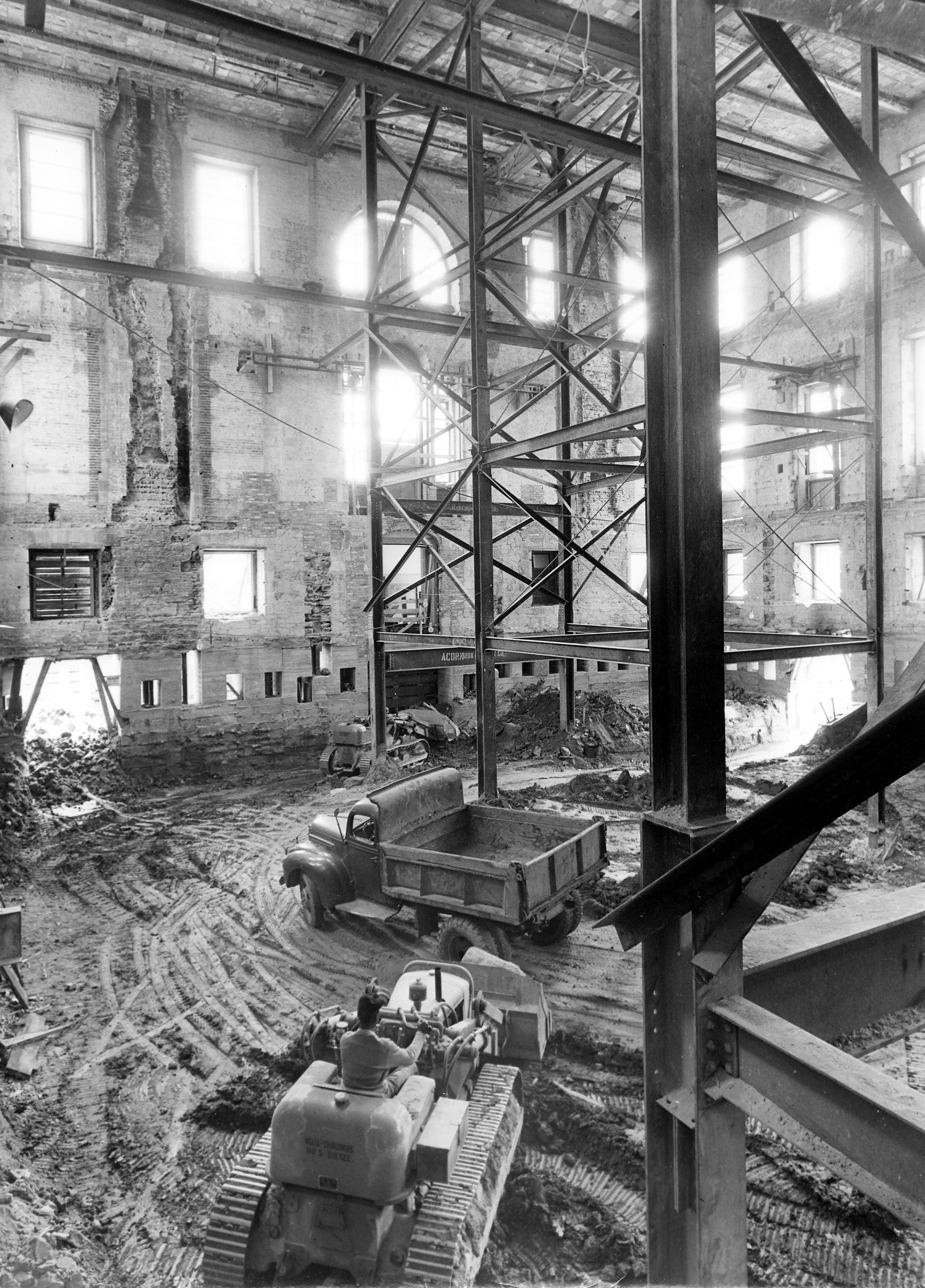 The shell of the White House during the renovation, as photographed on May 17, 1950. Window openings provide bursts of light into the cavernous interior of the White House, supported only by a web of temporary steel supports. The exterior walls rest on new concrete underpinnings, which allow earth-moving equipment to dig a new basement. Photo from the holdings of the National Archives and Records Administration, cataloged under the National Archives Identifier (NAID) 6982099.
