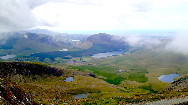 View from the top of Mount Snowdon with lakes and green hills.