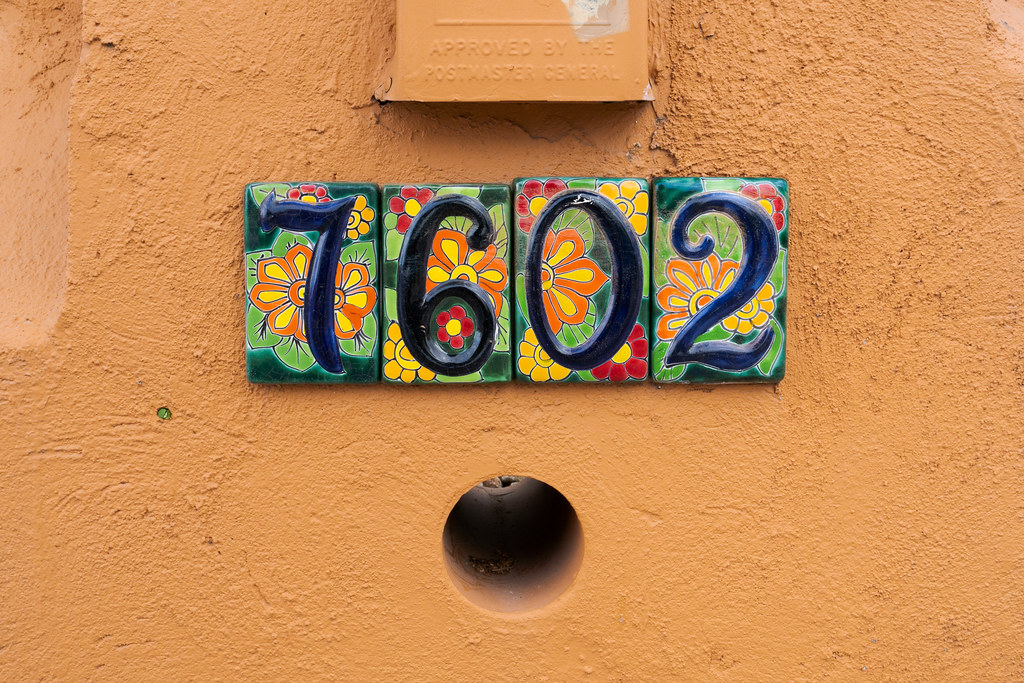 An opening for delivery of newspapers below decorated tile that shows the street address of a mailbox in the Buenavante neighborhood of Scottsdale, Arizona