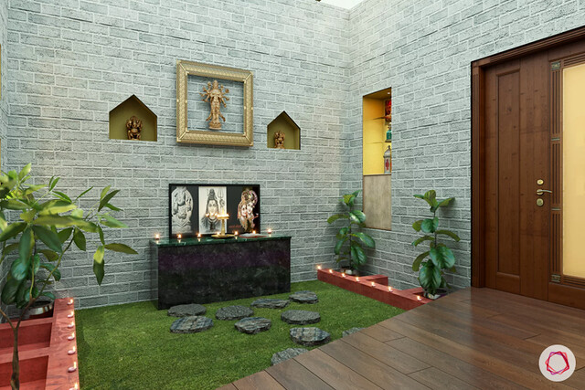 A stone clad wall as backdrop for a pooja room in a villa