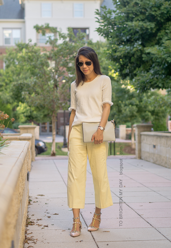 white sweater tee with fringe, two tone watch, silver cuff, morganite ring, yellow cropped wide legged pants, watercolor flats with studs