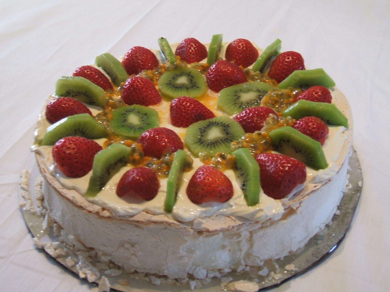 A pavlova dessert decorated with strawberries, passionfruit, kiwifruit and cream. Photo taken on November 25, 2007.