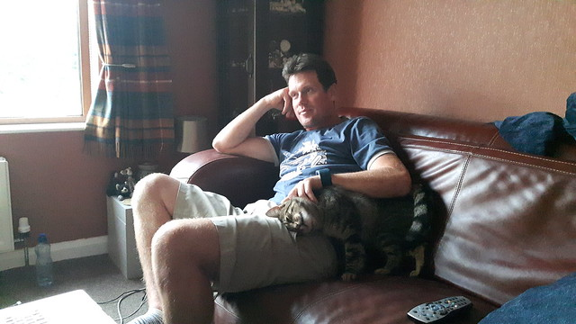 Terry and a cat cuddling on a sofa.